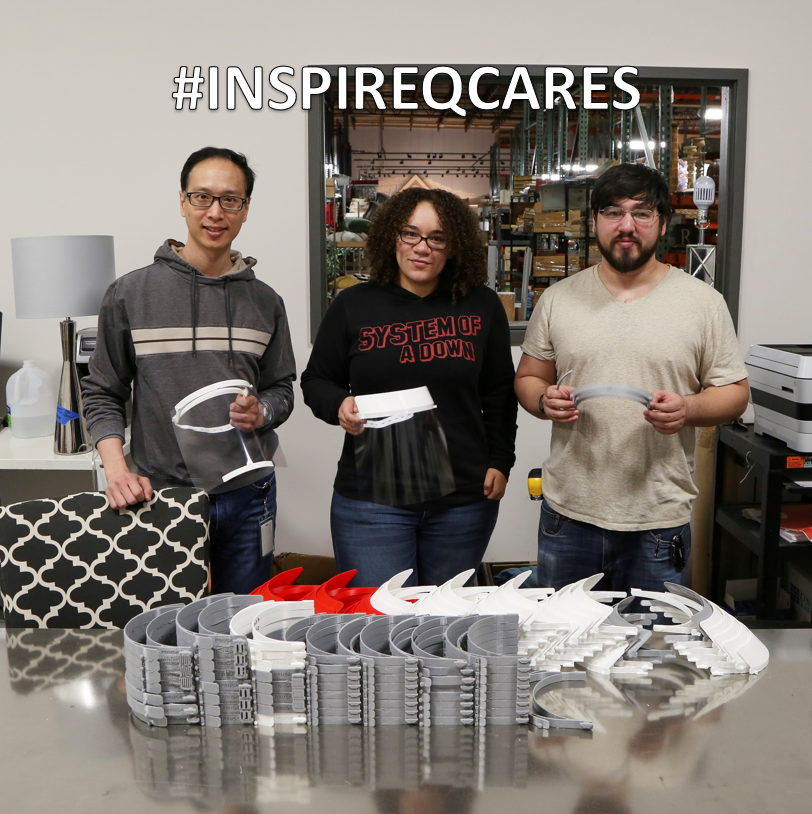 Three members of our Design Team smile and pose with dozens of face shields created from our 3D printer.