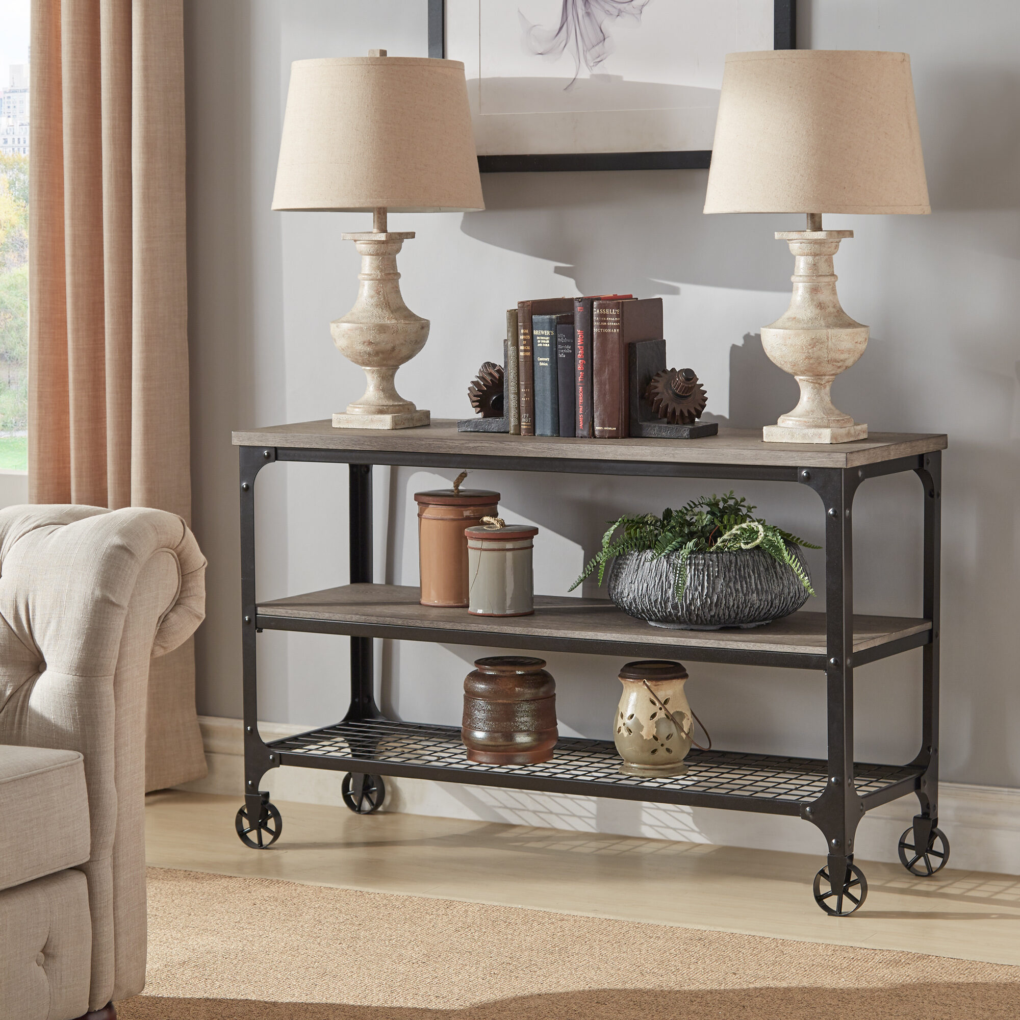 If you have the space, or hall trees are not your cup of tea, then try using a console table in your entryway! This is our Nelson Industrial Modern Rustic Console Sofa Table TV Stand by iNSPIRE Q Classic. It has three shelves, two of which featuring a weathered wood finish while the bottom shelf matches the metal frame.