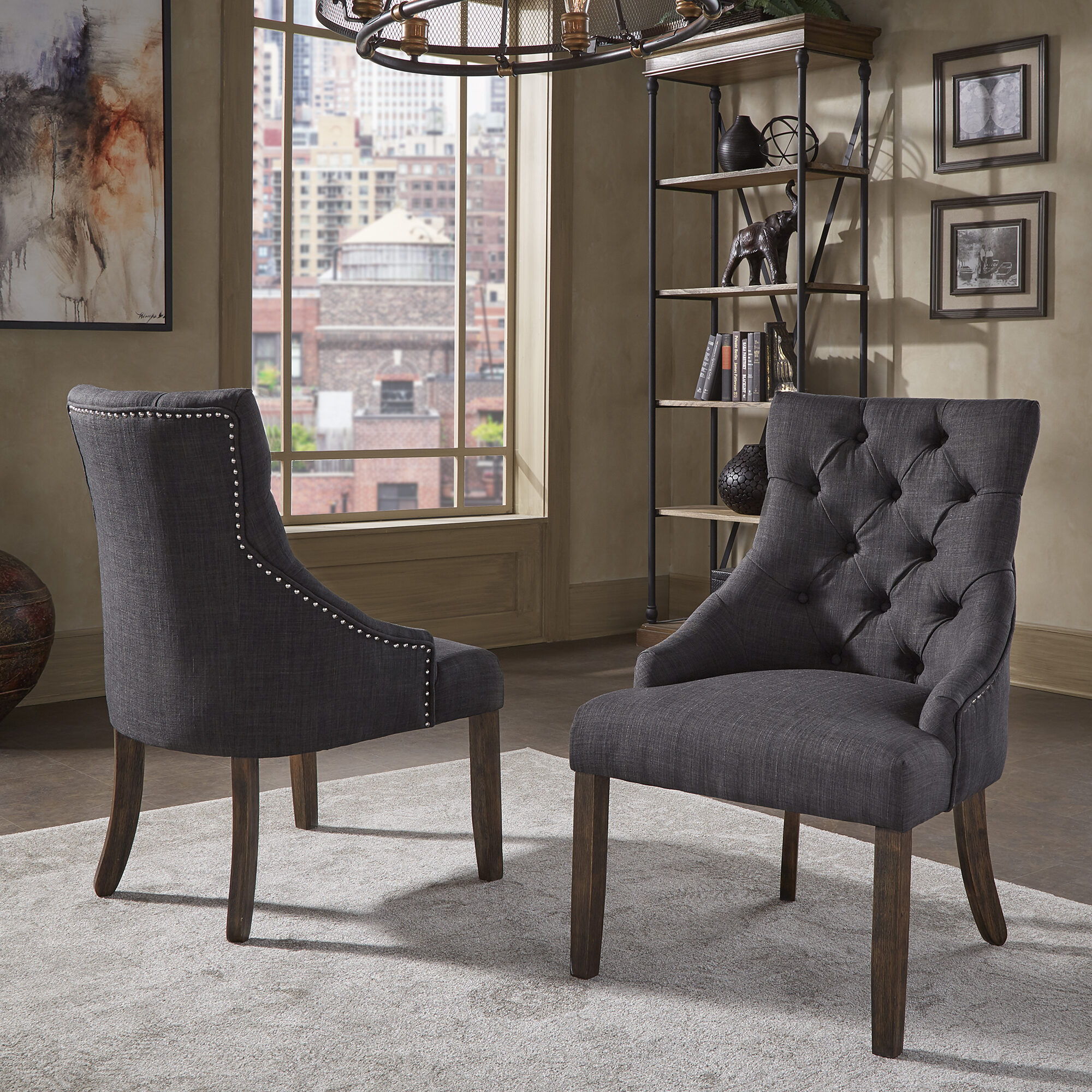 This is the companion to the desk: the chair. This is our Kimpton Linen Curved Back Tufted Dining Chair (Set of 2) by iNSPIRE Q Artisan. This chair has a button-tufted back, a curved wingback design, and linen upholstery. The linen upholstery comes in grey, dark grey, and beige. These chairs also have a brown finish on the exposed wooden legs.