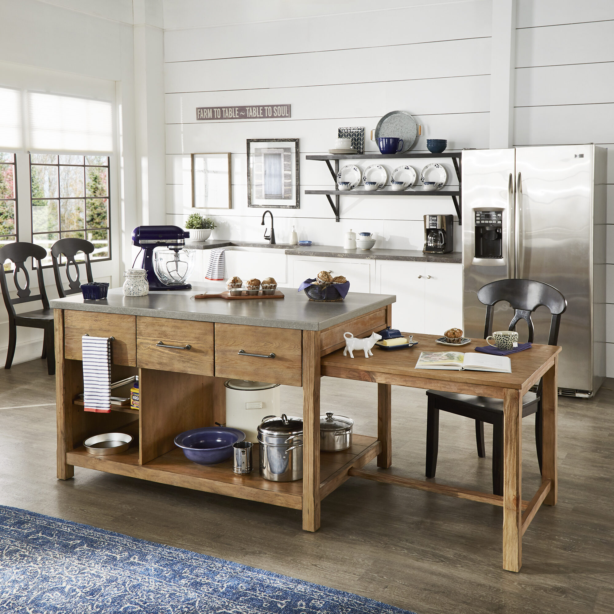 Our first back-to-school tip for parents centers on organizing your kitchen. This is our Tali Reclaimed Wood Extendable Kitchen Island by iNSPIRE Q Classic. It features a concrete surface with a wooden, oak-finished base, as well as an extendable table on the side.