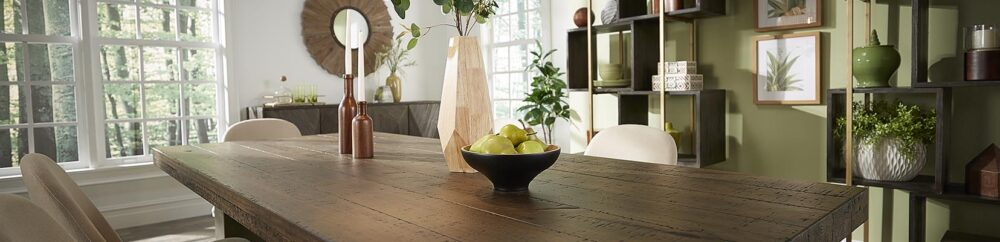 A dining room is displayed with an emphasis on greenery and wood tones for furniture and decor.