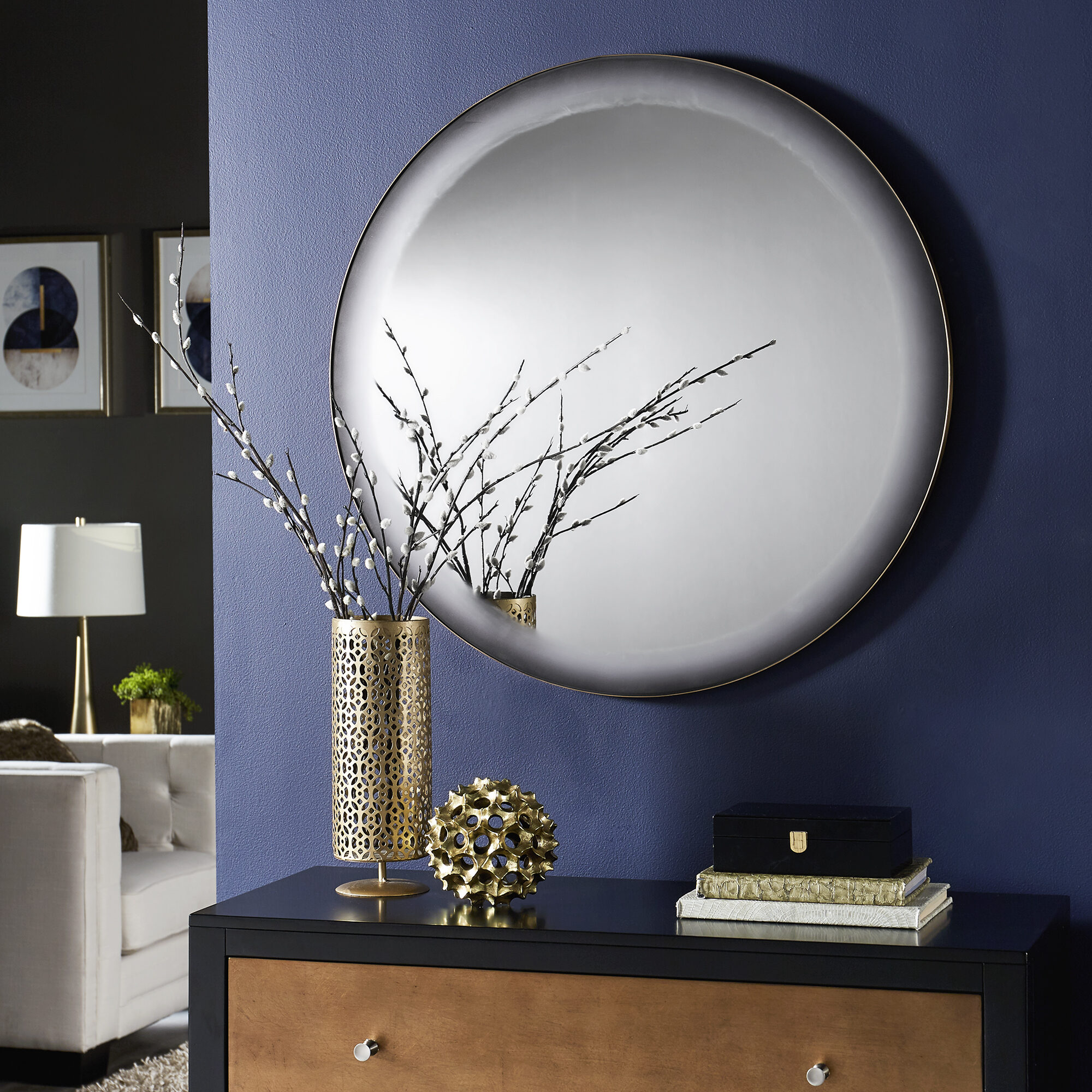 This grey-frosted edge round wall mirror is hung over a dresser. It adds visual interest to the room while still providing a spot for touching up appearances.