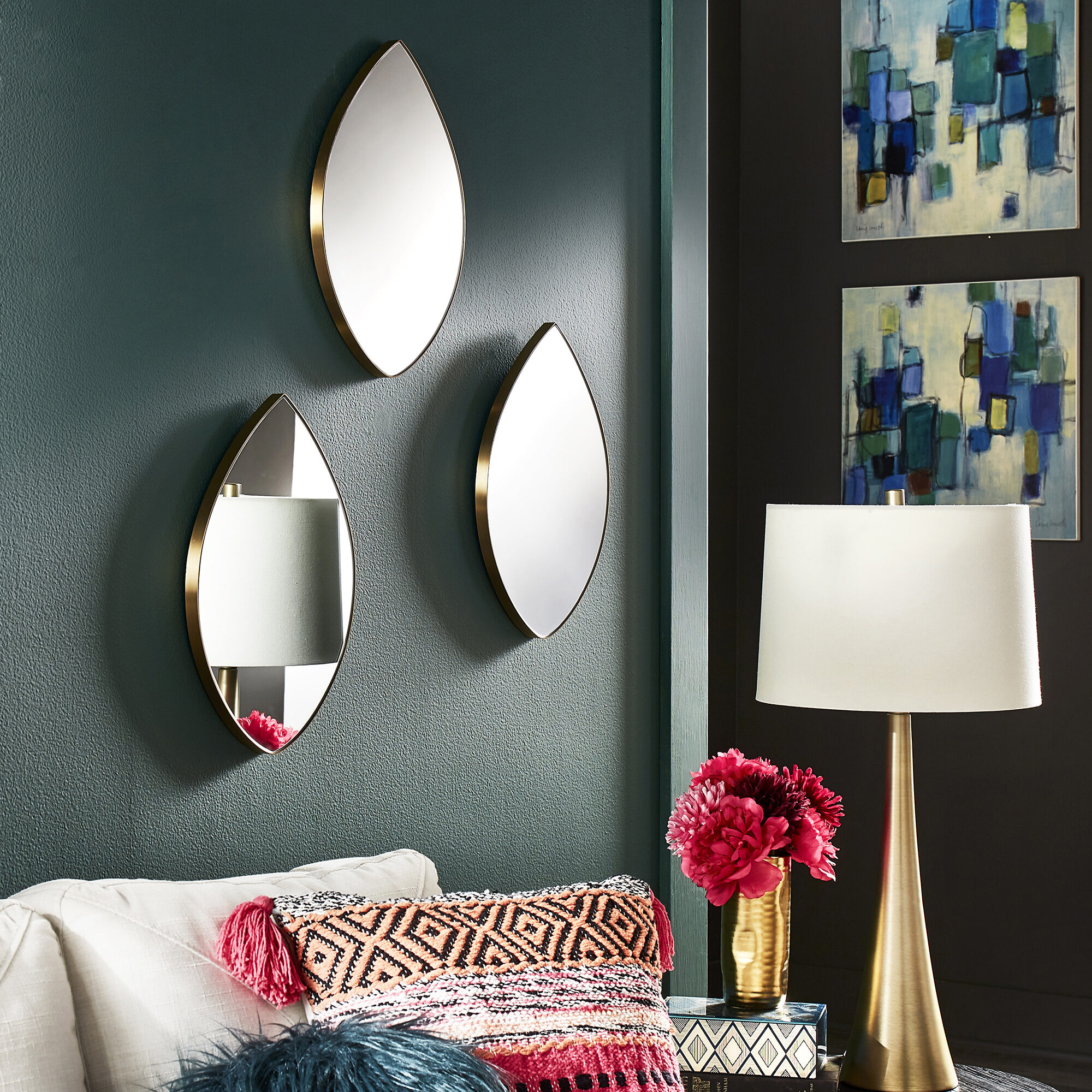 This image shows one mirror decorating idea. Three teardrop-shaped mirrors are styled on a wall behind a sofa and a table lamp to cast more light in the room.