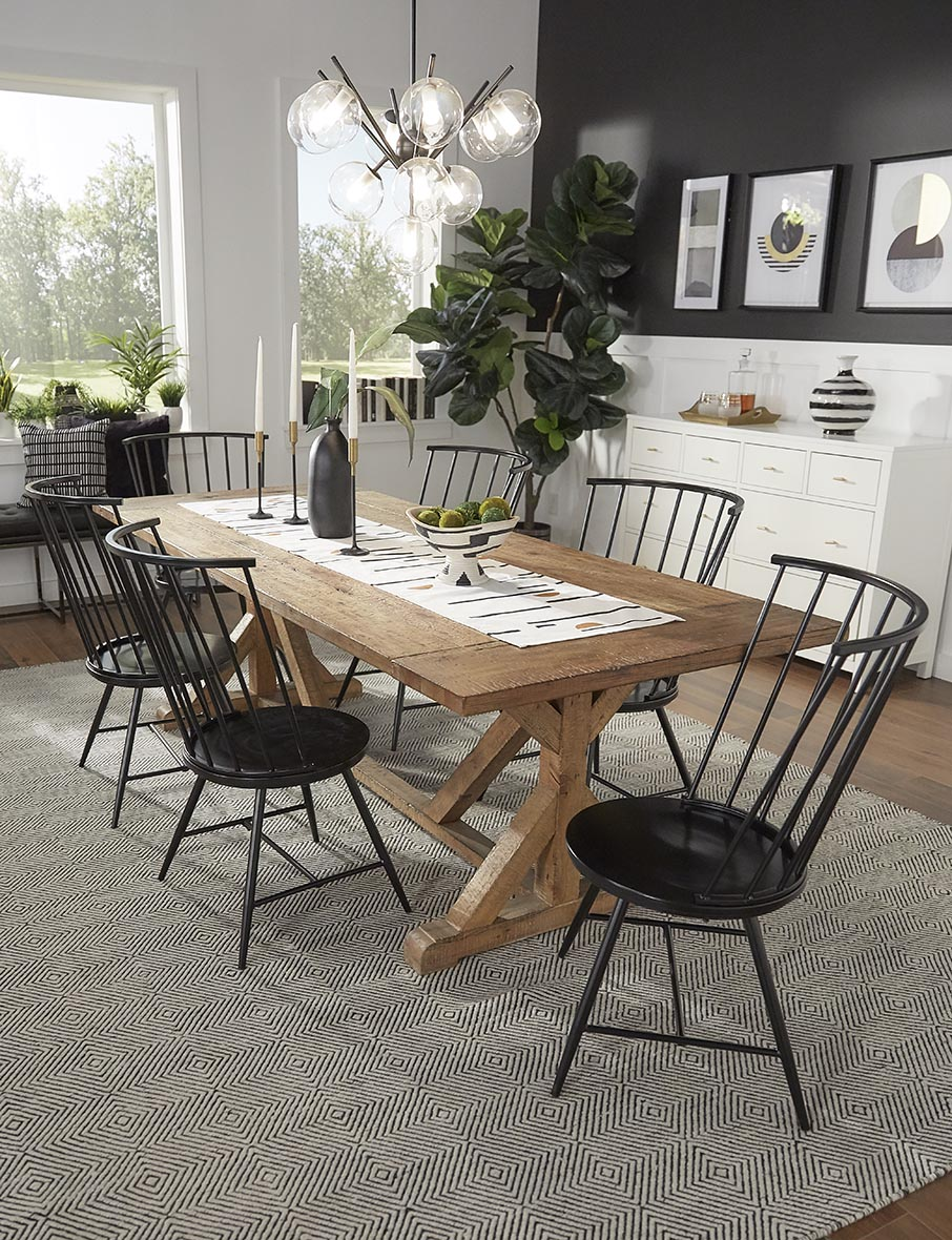 We chose to use a large, rectangular, reclaimed wood dining table to anchor our black and white dining space. We paired black chairs with this table to keep with the black and white theme.