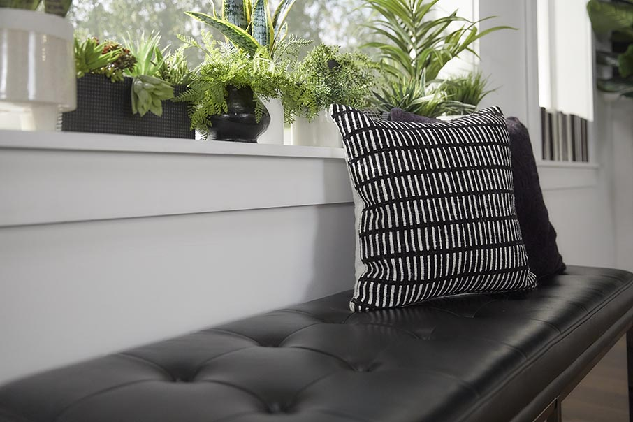 You can experiment a lot with textures in your dining space, and we recommend choosing textured decor to enhance your aesthetic. In this picture, we have a black leather-cushioned bench paired with two black and white textured throw pillows.