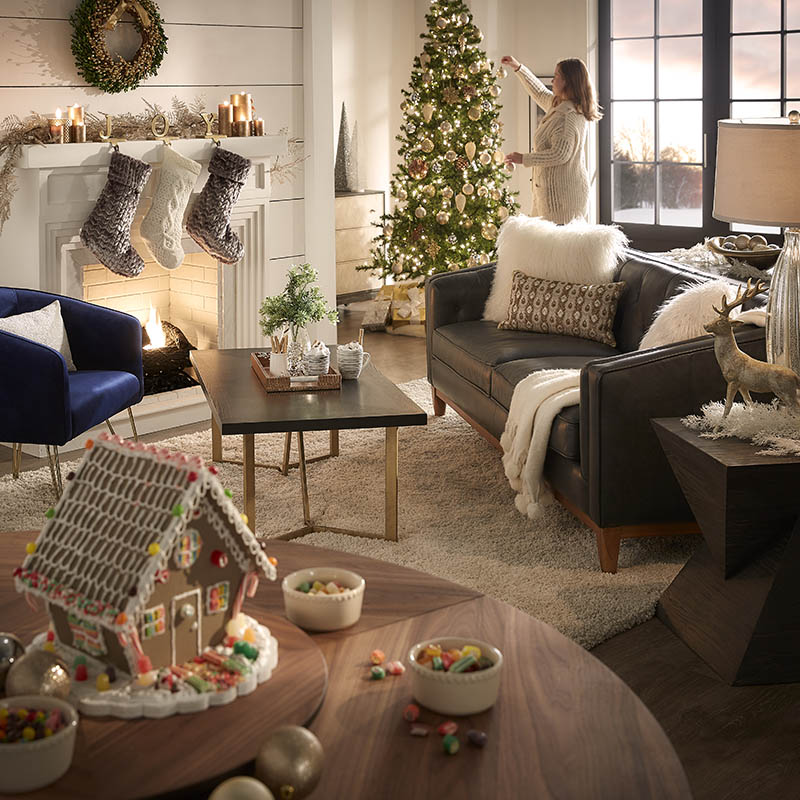 This image captures our entire family room! There is the lit fireplace, the coffee table and hot cocoa, the gingerbread house on the lazy susan dining table, and a black leather sofa with plush pillows and blankets. In the background is a Christmas tree decorated with white lights and ornaments, and a single person goes to hang the final ornament.