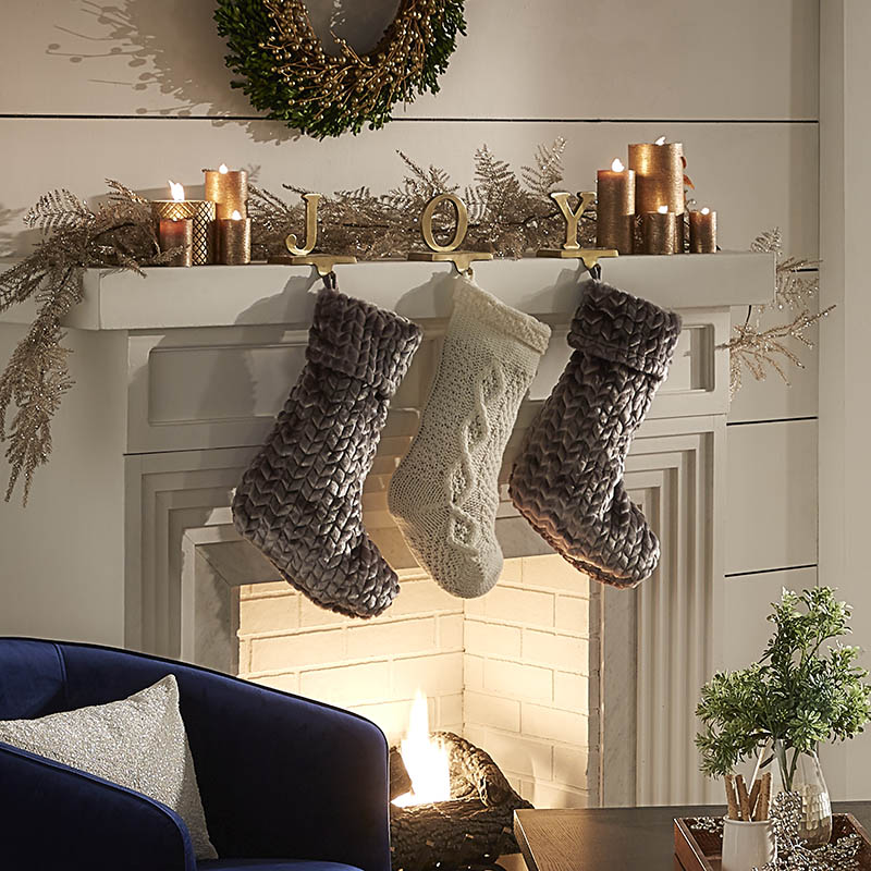 We anchored all of our holiday home decorating ideas with our fireplace! This image shows a lit fireplace with three plush stockings hanging over it. The mantle is decorated with lit gold candles, evergreen branches, and miniature statues of the the letters J, O, and Y.