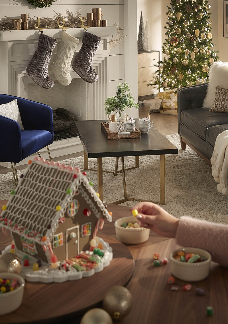 This shot features a decorated gingerbread house atop a lazy susan on our dining table. Someone is reaching to put the finishing touch on it. In the background is a coffee table with hot cocoa and our unlit fireplace.