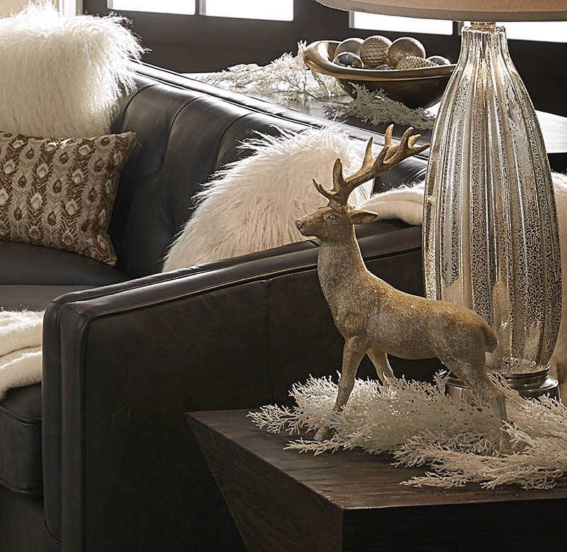 No need to be out with the old with our holiday home decorating ideas! This image shows a wood end table beside our black leather sofa. On top of the end table is a large lamp with frosted glass base. There is also a figurine of an antique-looking stag.