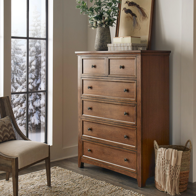 A close up of our 5-Drawer Wood Modular Storage Chest in an oak finish, perfect for our 2021 home decor trends. It is decorated with some pieces of home decor, including a vase of greenery.