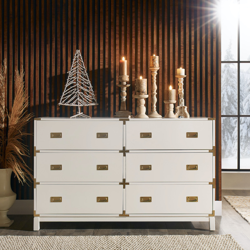 Pictured is our Kedric 6-Drawer Gold Accent Dresser by iNSPIRE Q Bold in a white finish. Keeping with the home decor trends, the dresser is decorated with some neutral-hued candles and a decorative silver tree figure. Behind the dresser is a wood textured accent wall.