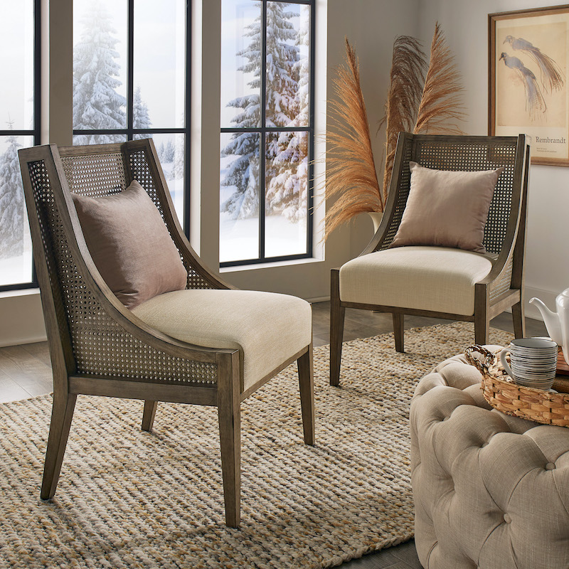 Pictured is our Antique Grey Oak Cane Accent Chairs (Set of 2) by iNSPIRE Q Modern. The seats are upholstered with beige fabric while we placed lush, light taupe accent pillows on them.