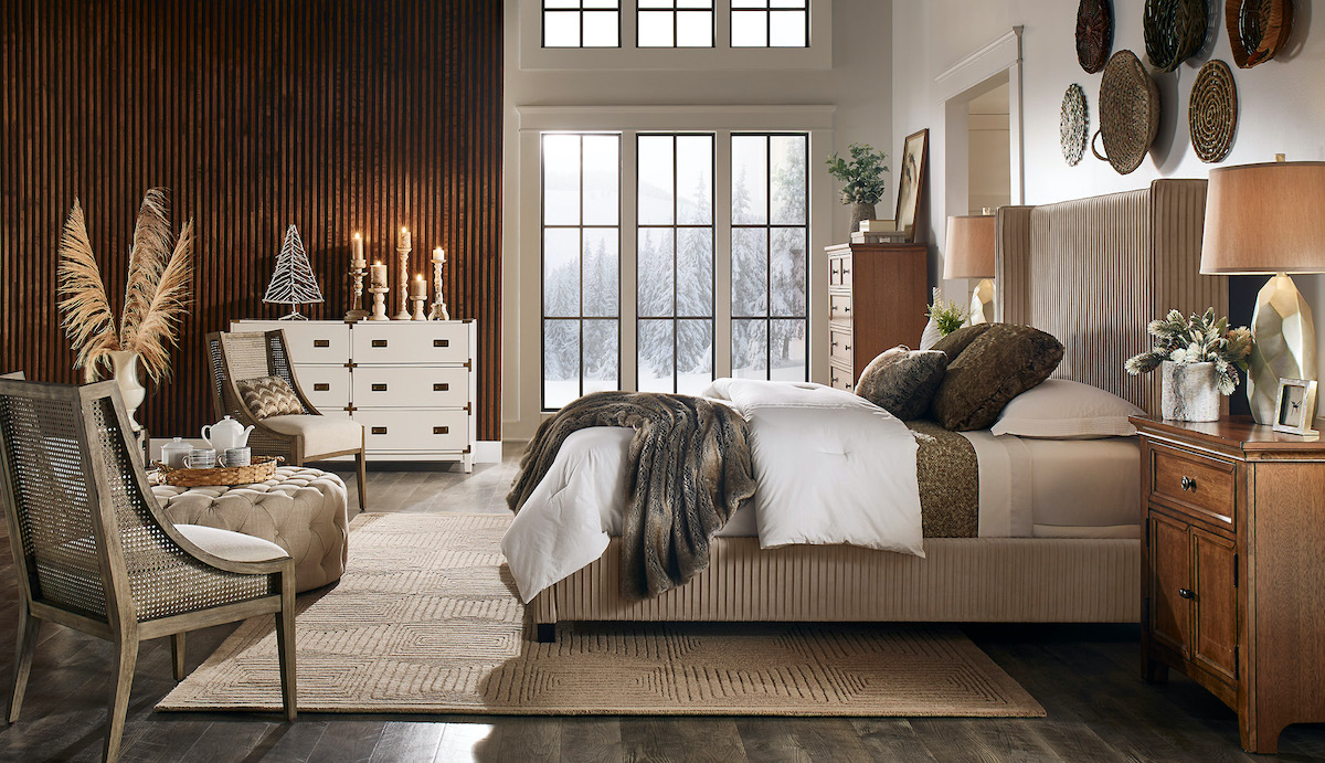 Pictured is our bedroom with all our home decor trends for 2021. The center of the room has a taupe velvet upholstered bed with two wood nightstands. The room also features a tall wood chest, a white and gold dresser, a beige button tufted cocktail ottoman, and two antique grey wood accent chairs.