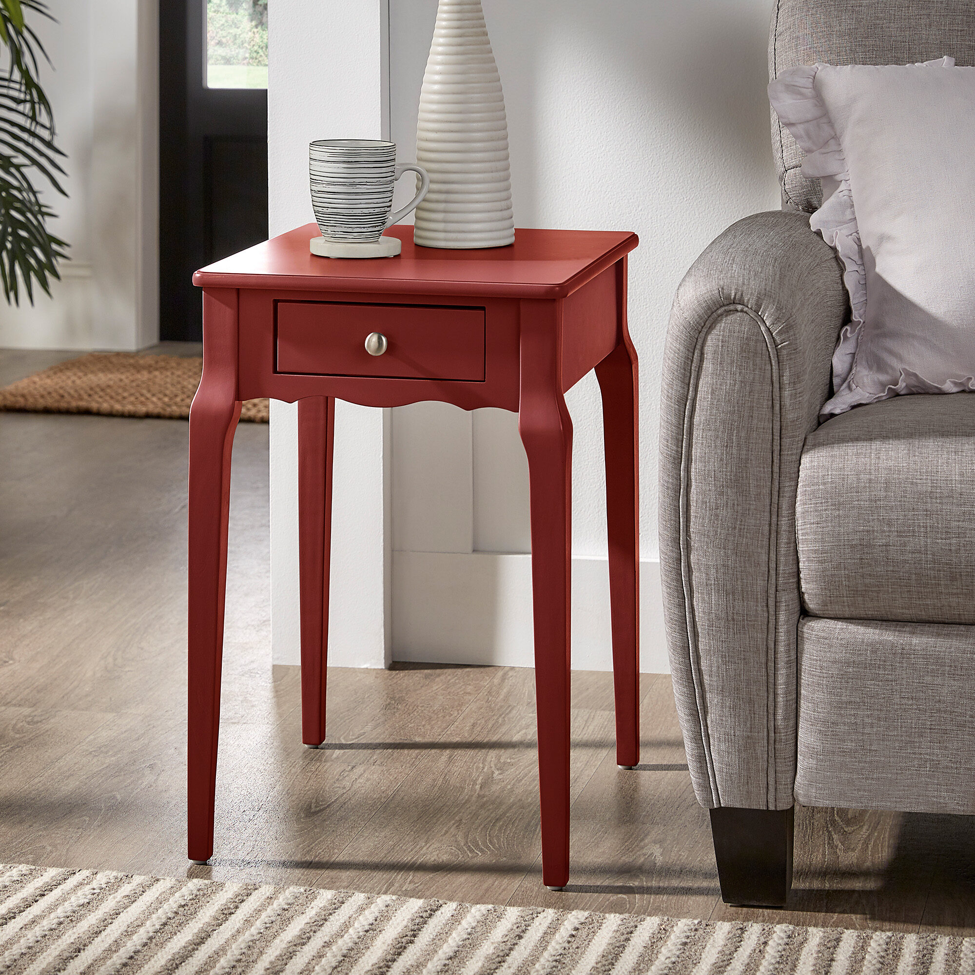 We used our samba red end table for this red home décor idea. This little end table has a single drawer with a silver knob drawer pull. This red piece is placed next to a grey fabric sofa and has a coffee mug sitting atop it.
