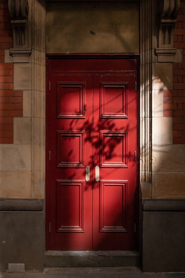 We have pictured a red-painted door placed against a brown stone building.