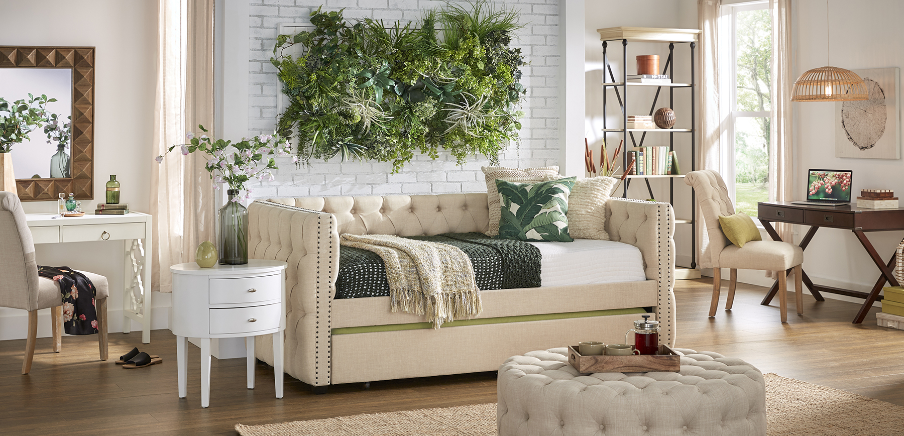 This image showcases the home decor trends of 2021. We feature our beige linen daybed, beige linen cocktail ottoman, white end table, white desk, espresso desk, and an antique white bookcase. This room also features natural elements like a faux greenery wall, wicker pendant light, sisal rug, and a reclaimed wood-framed mirror.