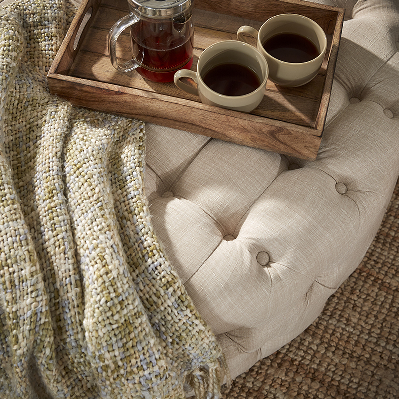 This image focuses on the cocktail ottoman. It shows the beige linen button tufting that the piece is upholstered in. On top of the ottoman is a wooden tray with cups of tea as well as a green knitted blanket. Underneath the ottoman is a light brown sisal rug.