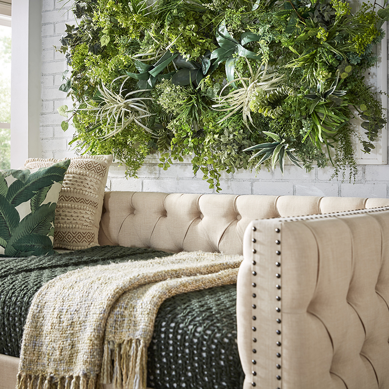 One of the biggest home decor trends of 2021 is about embracing biophilic design. This image shows a close up of the beige linen daybed. The daybed features green blankets and pillows for a fresh pop of color. It is set against an exposed white brick wall, which also features the faux greenery.