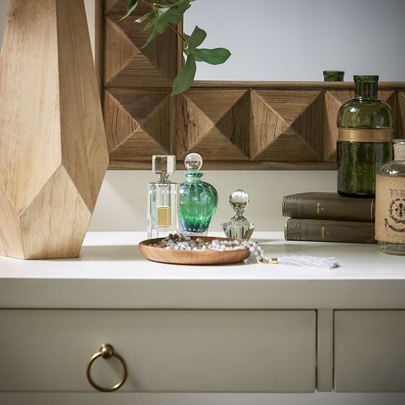 Our second desk, the white wood one, is used as a vanity. In this image, we have a reclaimed wood mirror mounted above the desk. The desk itself is decorated with green bottles of perfume and a wooden vase of greenery.