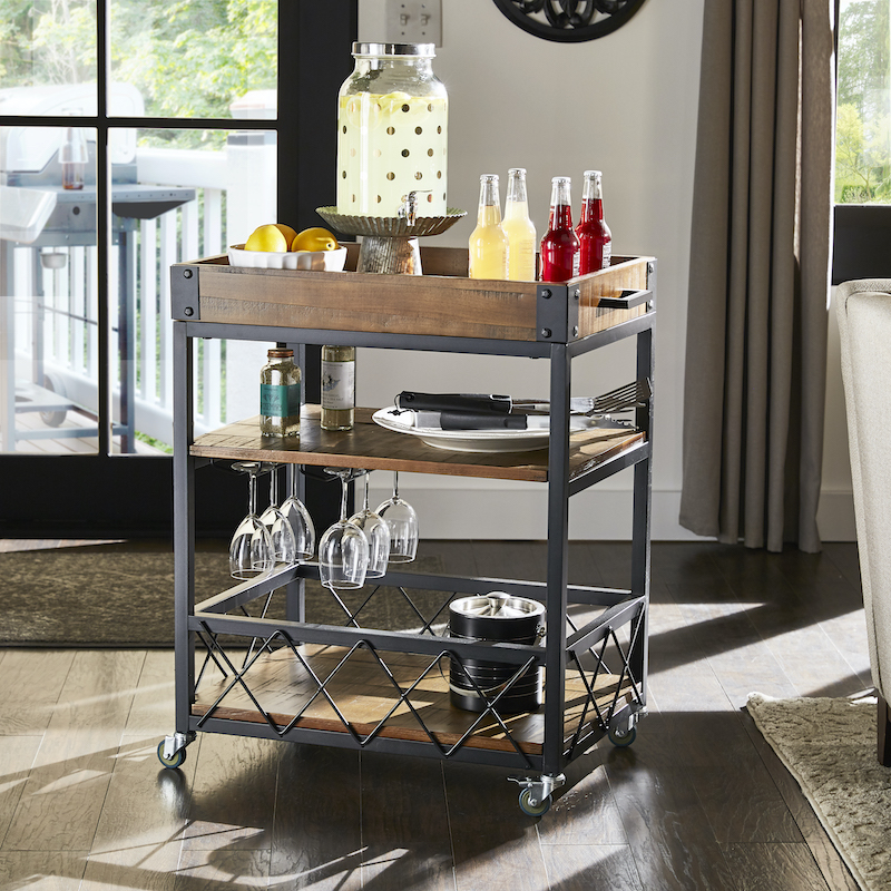 The most multifunctional piece of furniture one can own is a bar cart. Pictured here is a metal and wood bar cart with two shelves and a tray top. It offers enough space to store lemonade, wine glasses, and grilling tools.