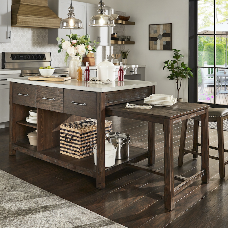 The extendable kitchen island is the star of our 2021 home decor trends. It is made with espresso-colored reclaimed wood with a concrete top. There are three drawers, three open shelves, and one extending table that can slide in and out of the island.