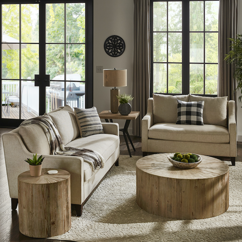 This image displays all our 2021 home decor trends in our living room. The sofa and matching loveseat are upholstered in beige fabric. The two end tables feature light, distressed reclaimed wood. The end table next to the sofa is cylinder-shaped while the end table next to the loveseat is square and has a black metal base. And in the center of the room is a coffee table that perfectly matches the cylinder end table. Potted plants and black and white accessories decorate the living room to make it stylish yet cozy.