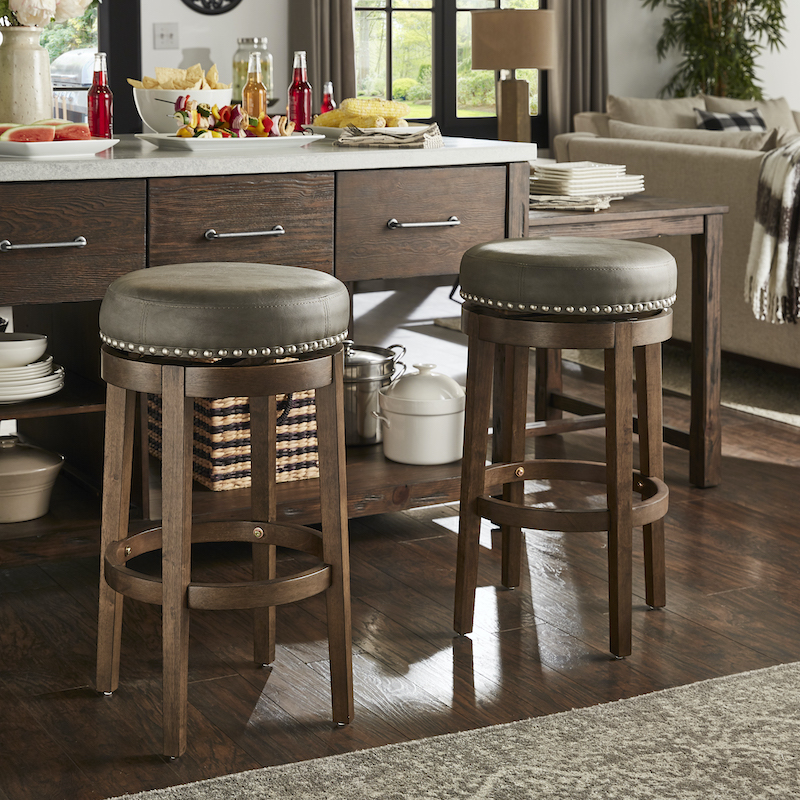 This image is a closeup of the backless barstools. The round barstools have brown wooden bases and grey faux leather seats. The seats also feature a nailhead trim for added visual interest to the overall neutral look.