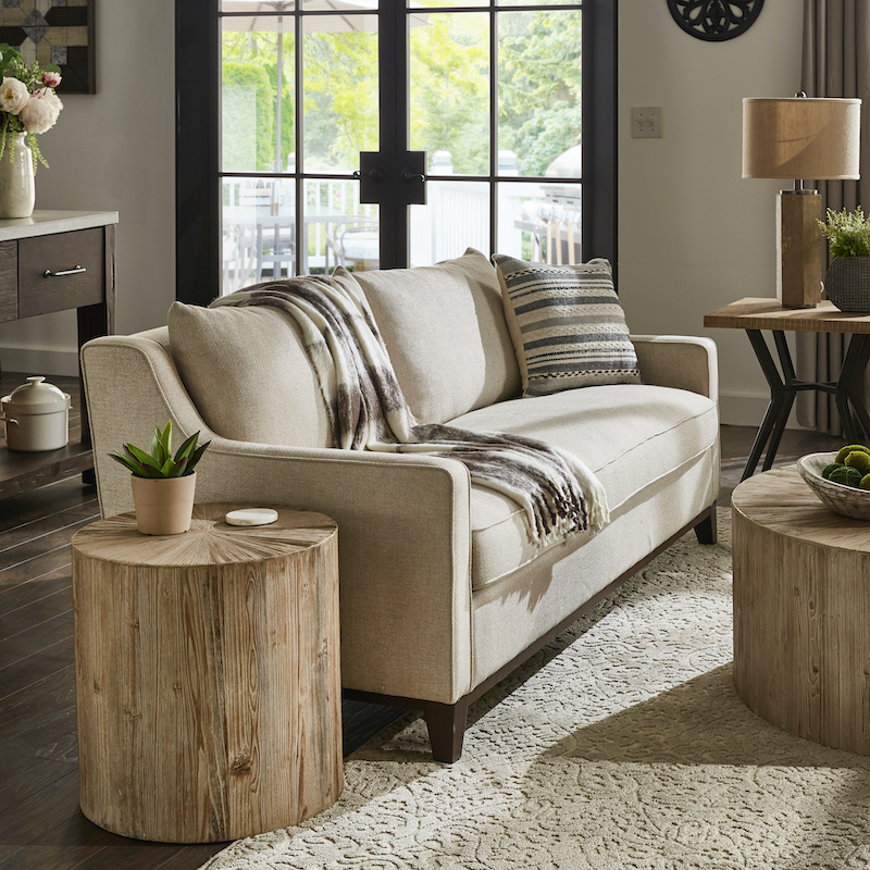 This is a closeup in our living room. We have a beige linen-upholstered sofa. Next to it is a light, distressed cylinder end table made with reclaimed wood. On top of the table is a potted succulent for a pop of color.