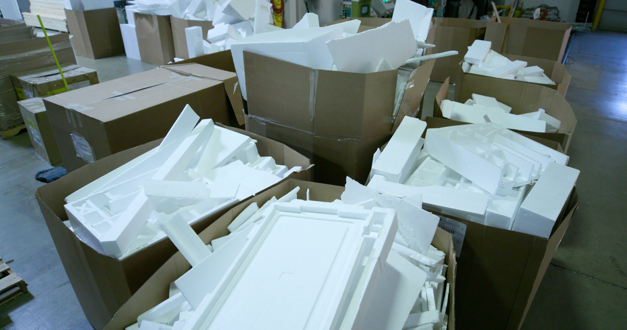 This image displays many cardboard boxes filled with Styrofoam pieces.
