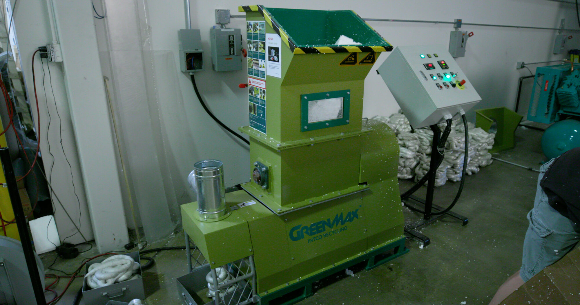 This is an image of the GREENMAX Melter Mars C50. It is a big green machine, over 5 feet tall and over 4 feet wide. There is a wide opening in the top for the Styrofoam to go through. This machine will help us reduce, reuse, and recycle our packaging waste.